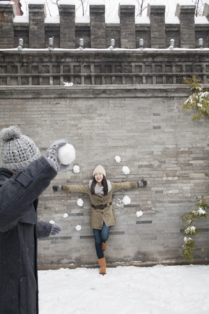 Young man throwing snow balls at young woman on wall photo