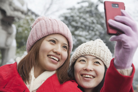 woman on phone: Two friends taking picture with cell phone in snow Stock Photo