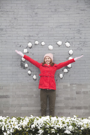 Young woman standing on wall with heart shaped snow balls photo
