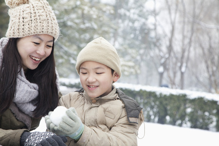 making earth: Mother helping son make snow ball