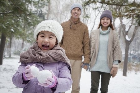 cogidos de la mano: Chica joven que lleva bolas de nieve delante de los padres en el parque en invierno Foto de archivo