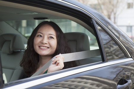 above 25: Young women in back seat of car fastening seat belt. Stock Photo
