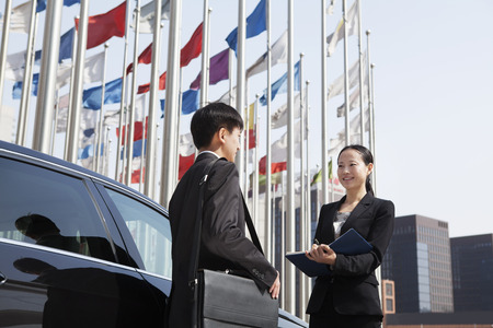 Two businesspeople meeting outdoors with flagpoles in background. Stock Photo