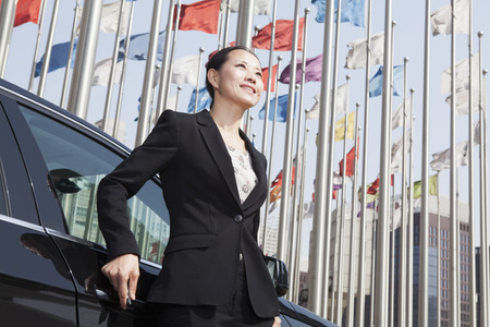 flagpoles: Businesswomen standing near car with flagpoles in background.