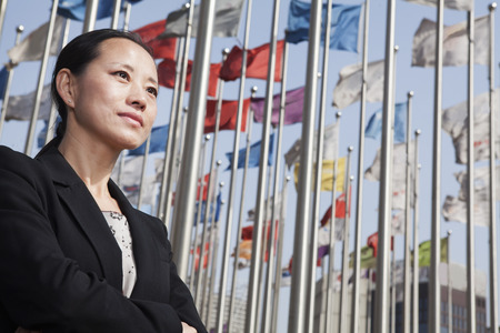 flagpoles: Businesswomen standing with arms crossed with flagpoles in background.