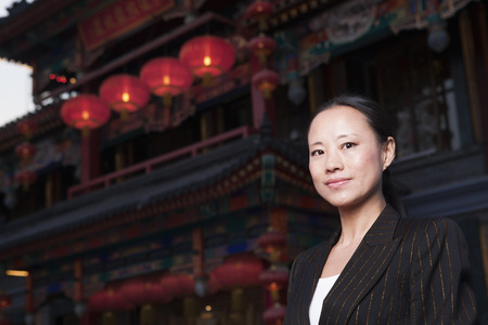 above 30: Portrait of businesswomen with Chinese architecture in background.