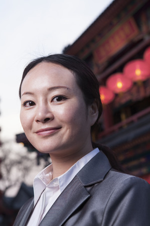 above 25: Portrait of businesswomen with Chinese architecture in background.