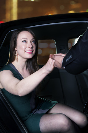 Young, glamorous woman being helped out of her car at a red carpet event in Beijing photo
