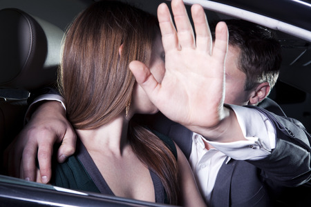 red carpet event: Young couple kissing in car at a red carpet event, man is shielding with his arm outstretched blocking paparazzi photographers Stock Photo