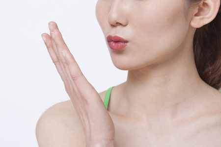 above 21: Close up of young woman blowing a kiss, studio shot  Stock Photo
