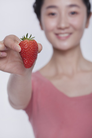 above 21: Young smiling woman in pink shirt holding and showing a strawberry
