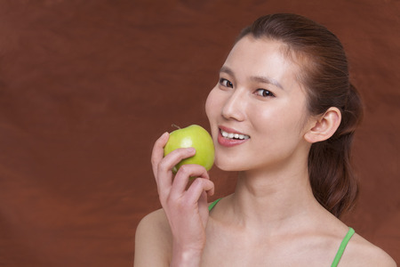 above 21: Young woman holding a apple and getting ready to take a bite, looking at camera, studio shot Stock Photo