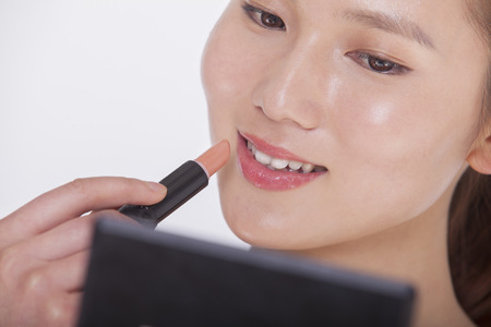 above 21: Close up of young woman applying lipstick in a mirror, studio shot Stock Photo