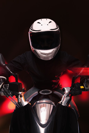 crash helmet: Young man riding a motorcycle at night through the streets of Beijing, front view