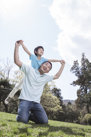 flying man: Father playing with son in park.