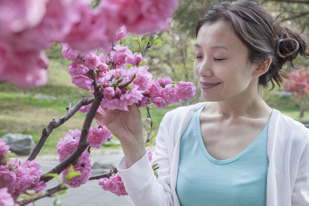above 30: Woman smelling cherry blossoms with eyes closed.