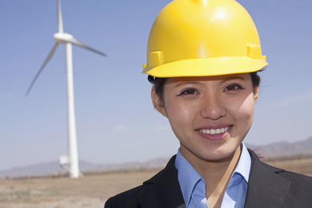 above 21: Portrait of young smiling female engineer checking wind turbines on site Stock Photo