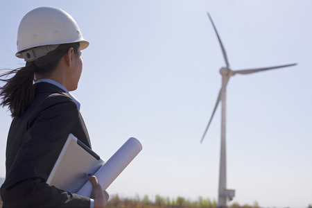 conservation: Young female engineer holding blueprints and checking wind turbines on site,  Stock Photo