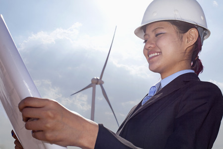 energy work: Young smiling female engineer holding open and looking down at blueprints, on site with wind turbines Stock Photo