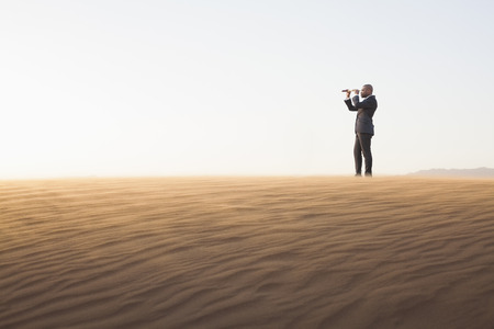 Young businessman looking through telescope in  the middle of the desert photo