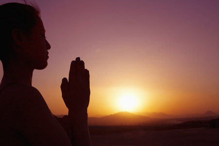 clasped hands: Serene young woman with hands together in prayer pose  in the desert in China, silhouette, sun setting, profile