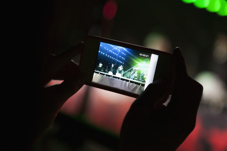 entertainment event: Young woman taking a photography with her smart phone at an indoor concert, Close-up on hands
