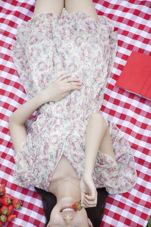 above 18: Midsection of a young woman lying on her back on a checkered blanket eating strawberries