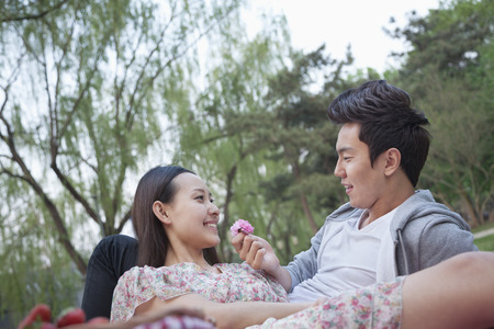 above 18: Smiling couple in love having a picnic in the park, lying down on the blanket and holding a flower blossom