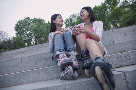 concrete steps: Two young friends with roller blades sitting and resting on concrete steps outdoors