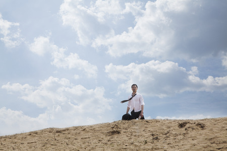 Young businessman lost and walking through the desert, distant  Stock Photo
