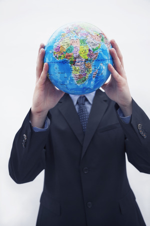 obscured: Businessman in a suit holding up a globe in front of his face, obscured face, studio shot