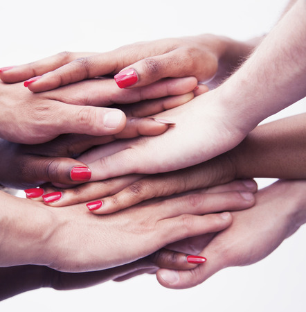 above 18: Close-up on a pile of hands on top of each other, multi-ethnic group of people, studio shot Stock Photo