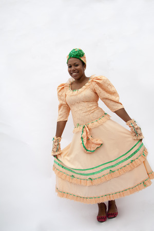 above 21: Portrait of young smiling woman holding her skirt in traditional clothing from the Caribbean, studio shot Stock Photo