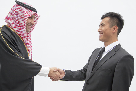 above 21: Smiling businessman and young man in traditional Arab clothing shaking hands, studio shot
