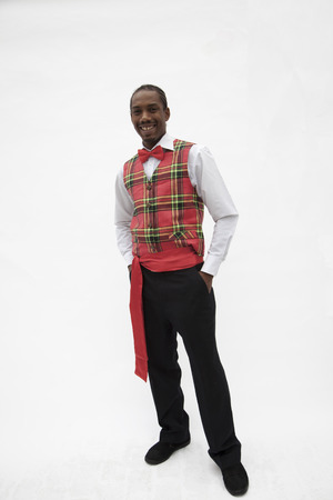Portrait of young man in plaid vest and red bow tie, traditional clothing from Africa, studio shot photo