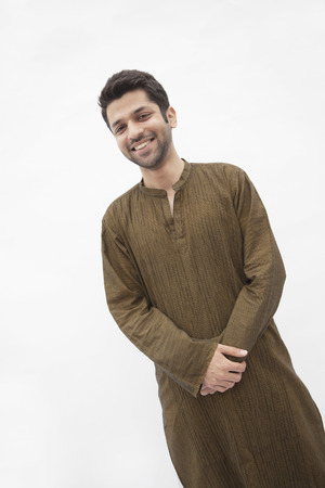 above 21: Portrait of smiling young man wearing traditional clothing from Pakistan, studio shot