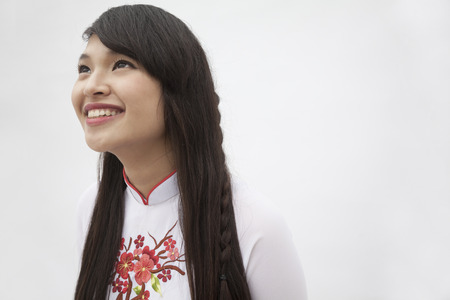 above 18: Portrait of smiling young woman with long hair wearing a traditional dress from Vietnam, studio shot