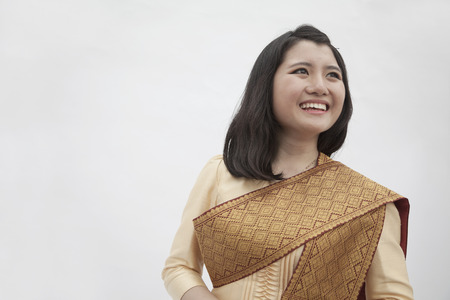 traditional culture: Portrait of smiling young woman in traditional clothing from Laos, studio shot