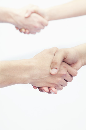 above 21: Four young people shaking hands, close-up, studio shot