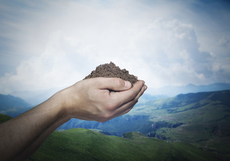 above 25: Hands holding a pile of soil with beautiful landscape in the background