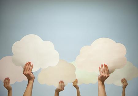 imaginacion: M�ltiples manos sosteniendo cortaron nubes de papel sobre un fondo azul, tiro del estudio