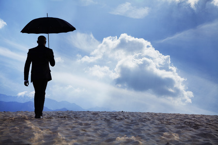 Businessman holding an umbrella and walking away in the middle of the desert with dreamlike clouds photo