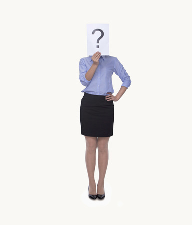 indecision: Young businesswoman holding at paper with a question mark on it, obscured face, studio shot