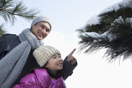 Father with daughter pointing at tree branch covered in snow