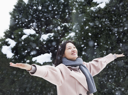 outstretched: Woman with arms outstretched feeling the snow