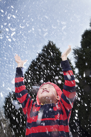 away from it all: Boy with arms raised feeling the snow