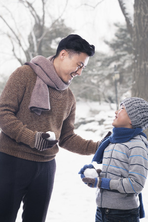 some under 18: Father and son holding snowballs Stock Photo