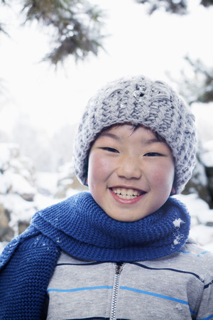 all under 18: Smiling boy in the snow, portrait