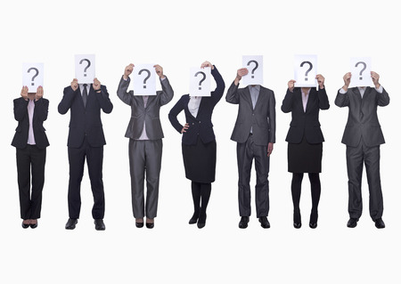 obscured face: Medium group of business people in a row holding up paper with question mark, obscured face, studio shot