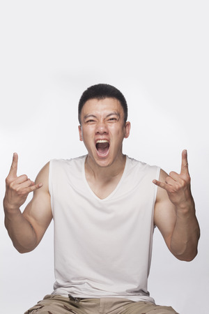 hand sign: Excited man making hand sign with mouth open, studio shot Stockfoto